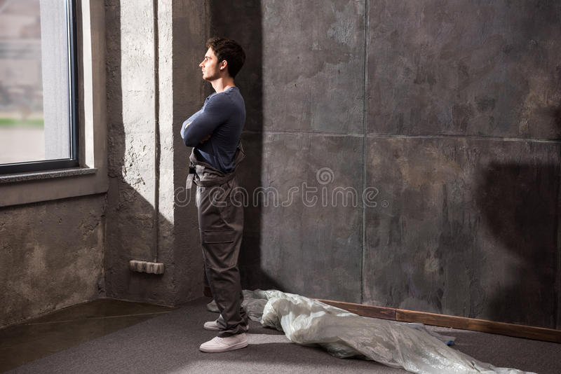 Pensive young construction worker standing near window and looking away stock photography