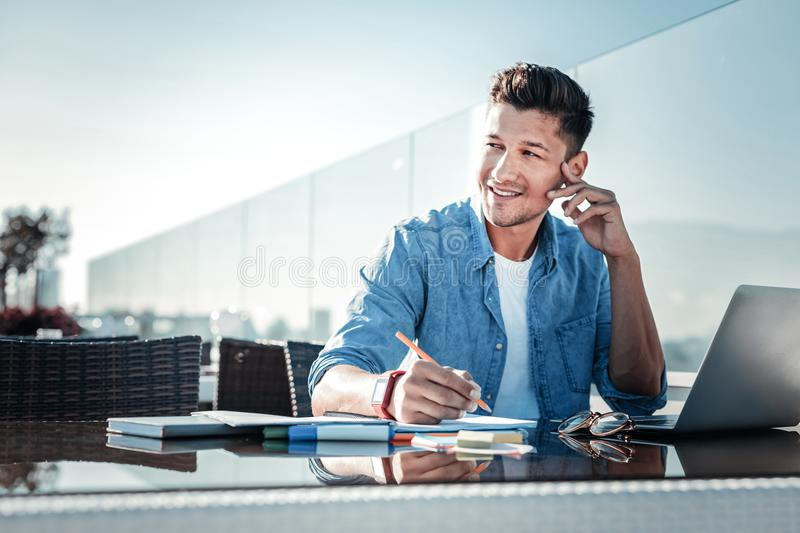 Pensive young gentleman smiling while working on laptop outdoors royalty free stock photos