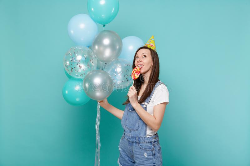 Pensive young girl in birthday hat looking up licking round lollipop celebrating hold colorful air balloons isolated on. Blue turquoise wall background royalty free stock photography