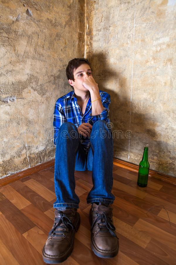 Sad Young Man. Pensive Young Man with a Beer by the Old Wall royalty free stock photos
