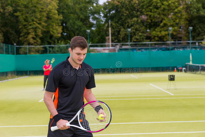 Pensive young man holding a racket outdoor on tennis court at ea royalty free stock photography