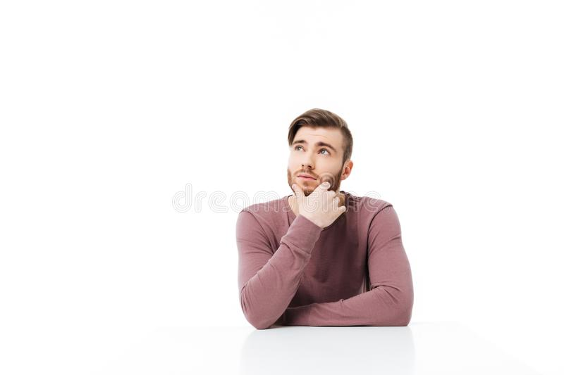 Pensive young man looking up dreaming sitting at the table isolated. Thinking pose. Pensive young man looking up dreaming while sitting at the table isolated royalty free stock images