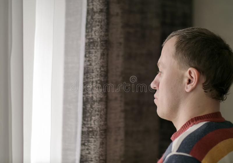 Pensive young man looks out the window stock photography