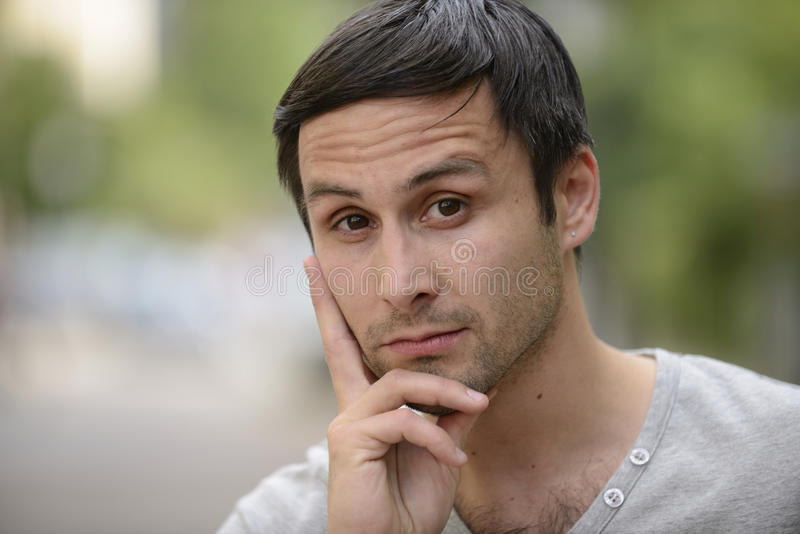 Pensive young man outdoors royalty free stock photo