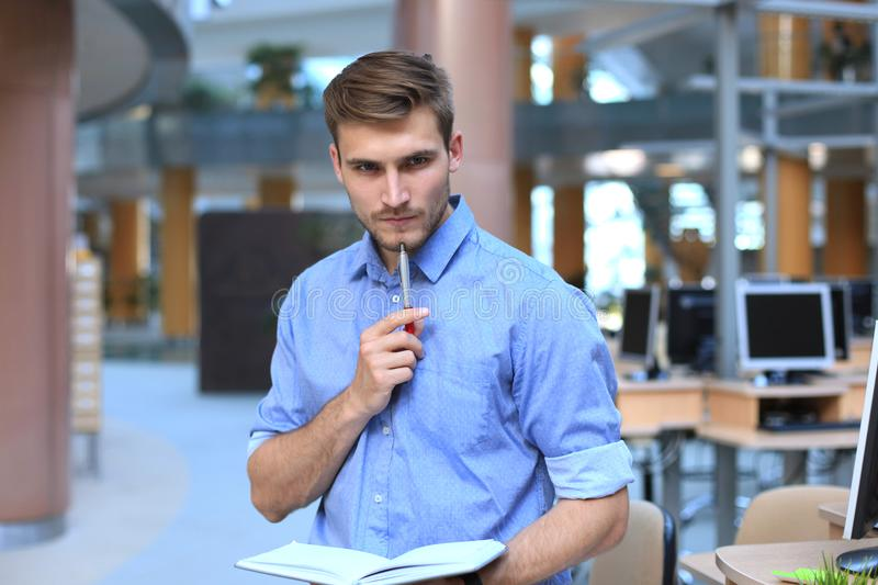 Pensive young man standing in his office. royalty free stock photo