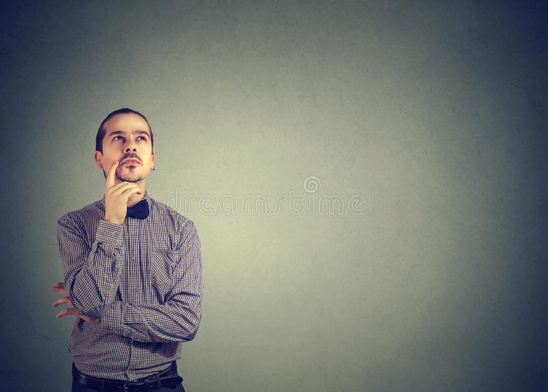 Pensive young man thinking looking up stock photography