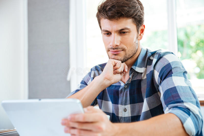 Pensive young man thinking and using tablet at home royalty free stock photo