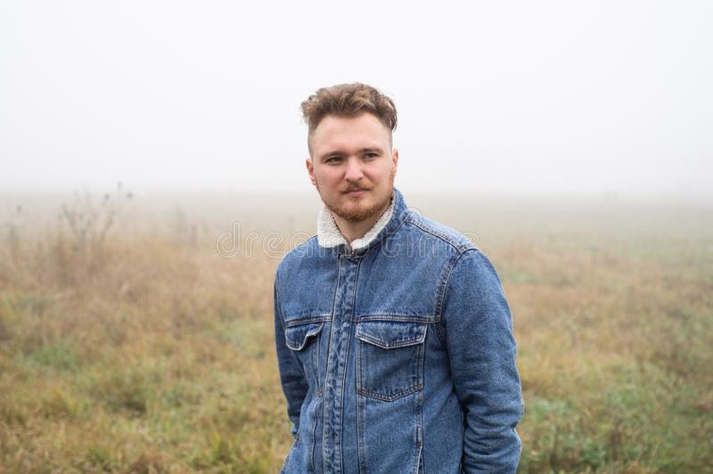 A pensive young stylish man with a mustache stands against gray misty nature background. stock photo