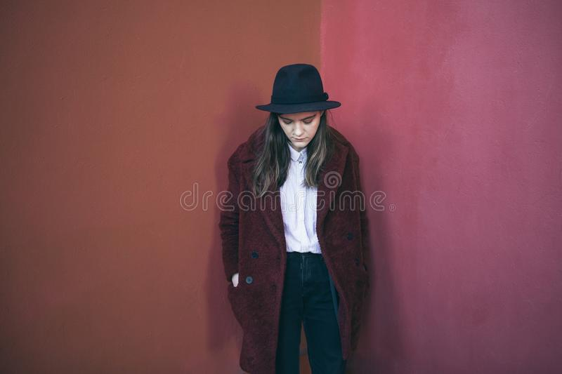 Pensive young teen girl stands against the red wall. Sad doubts. Melancholic mood to be alone with yourself. Pensive stylish young teen girl stands against the royalty free stock photo