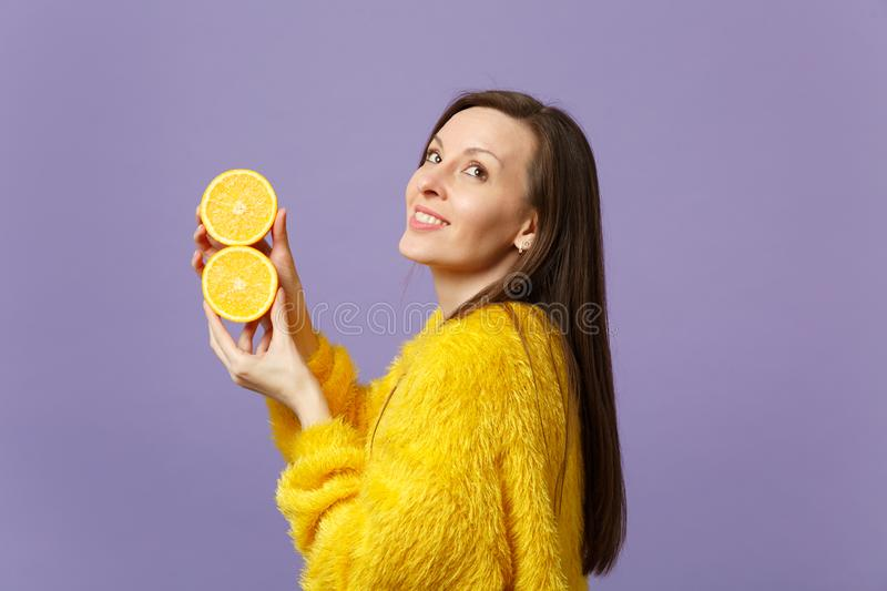 Pensive young woman in fur sweater looking up holding in hands halfs of fresh ripe orange fruit isolated on violet stock photography