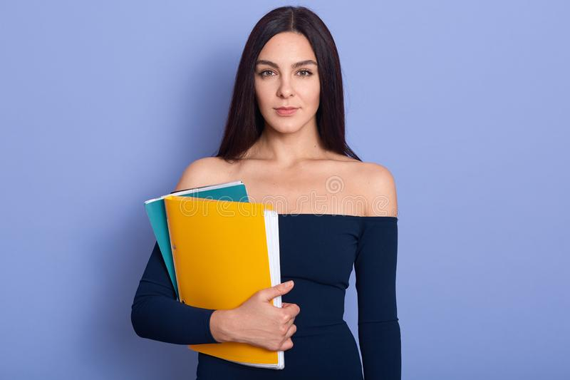 Pensive young woman holding paper folders in hands. Beautiful brunette woman wearing stylish dress standing isolated over blue royalty free stock photos