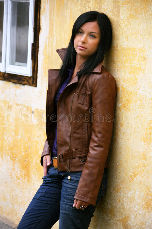 Pensive young woman at a house wall stock photo