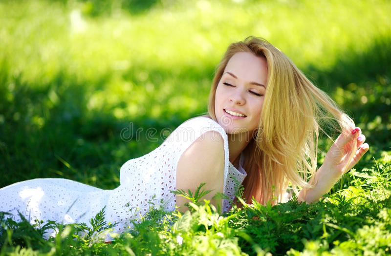 Pensive young woman lying in the green grass, enjoying summer day stock photos