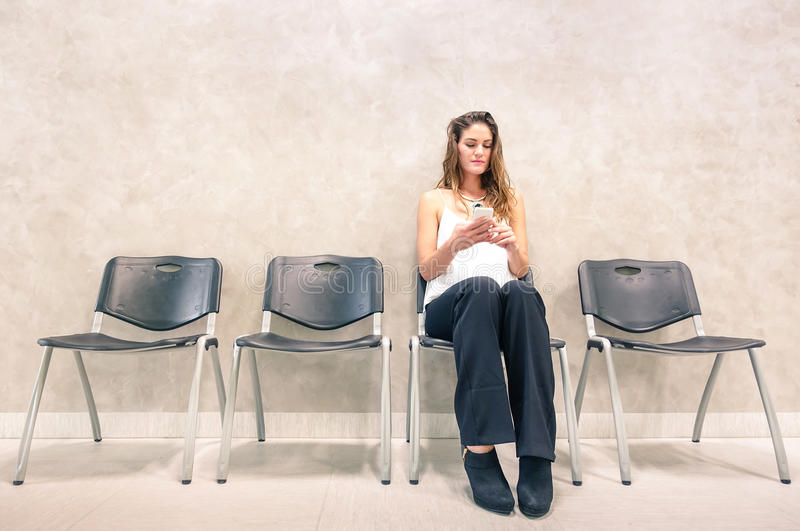 Pensive young woman with mobile smart phone at waiting room. Pensive young woman with mobile smart phone sitting in waiting room - Anxious female person using royalty free stock photo