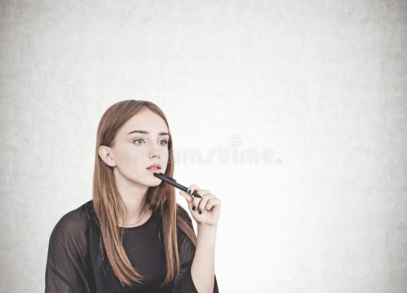 Pensive young woman with pen, concrete royalty free stock photos
