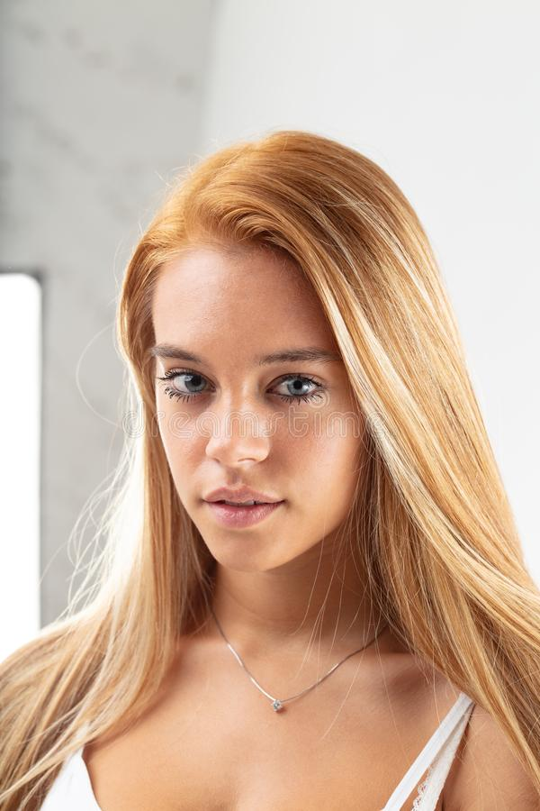 Pensive young woman scrutinising the camera. Pensive young woman with straight long blond hair standing scrutinising the camera with a serious expression stock image