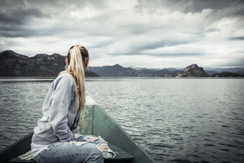 Pensive young woman tourist looking at beautiful landscape on bow of boat floating on water towards shore in overcast day with royalty free stock images