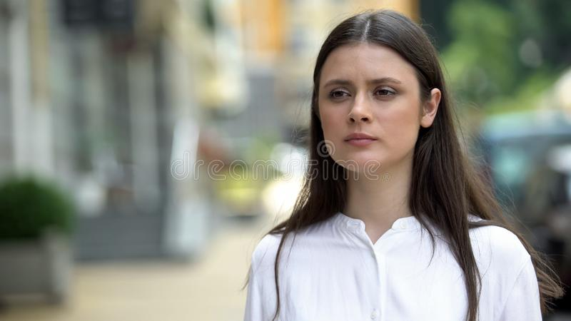 Pensive young woman waiting on city street, meeting with boyfriend after work royalty free stock image
