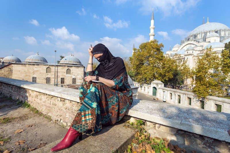 Pensively patrzeć Bliskowschodniego damy obsiadanie w parku zdjęcie stock