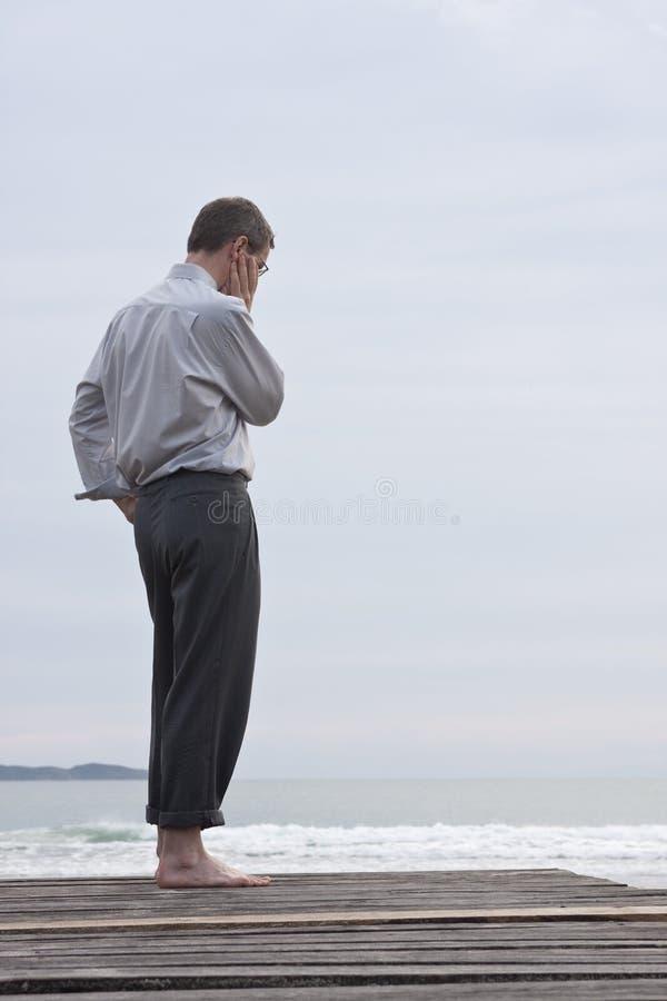 Pensiver Geschäftsmann am Strand stockfotos
