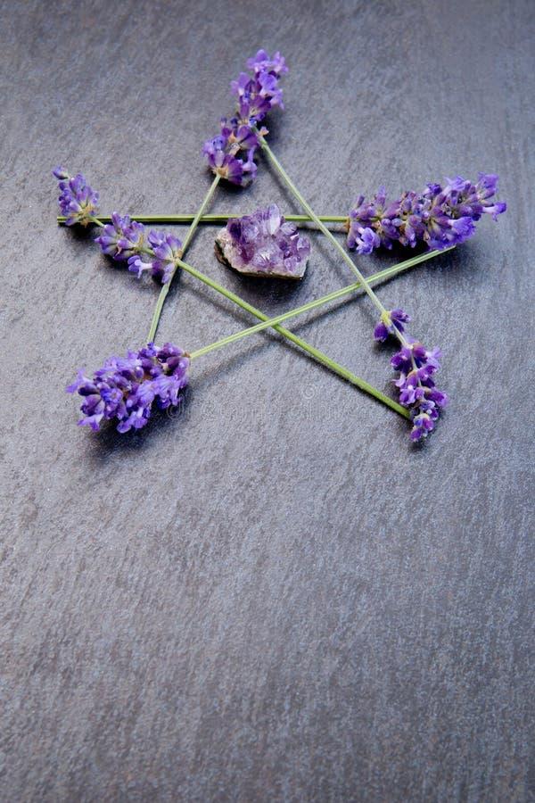 Pentagram - a bruxa, Wicca, símbolo pagão fez de pontos roxos da flor da alfazema com conjunto da ametista fotos de stock royalty free
