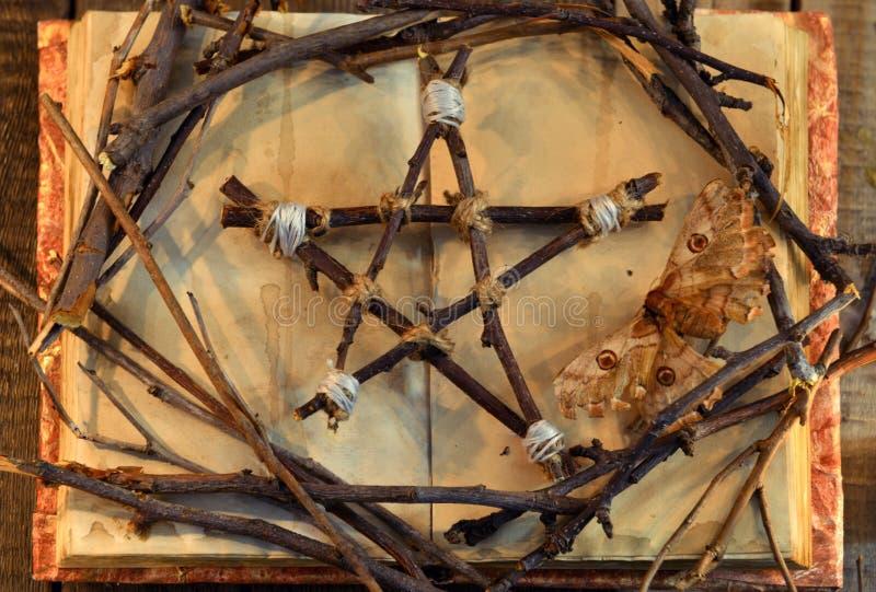 Pentagram de Wicca, polilla - símbolo de la muerte, y ramas de árbol en el libro abierto con las páginas lamentables en la luz de foto de archivo