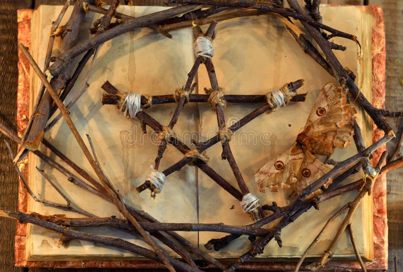 Pentagram de Wicca, traça - símbolo da morte, e ramos de árvore no livro aberto com as páginas gastos na luz da vela, vista super foto de stock