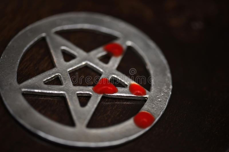 Pentagram with drops of blood lies on a wooden background. black mass. black magic ritual. Old pentagram with drops of blood lies on a wooden background. black stock photography