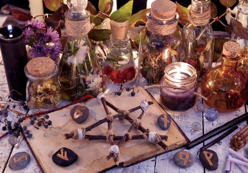 Pentagramma di legno, bottiglie di vetro, del libro aperto, fiori, candele e rune sulla tavola della strega immagini stock libere da diritti