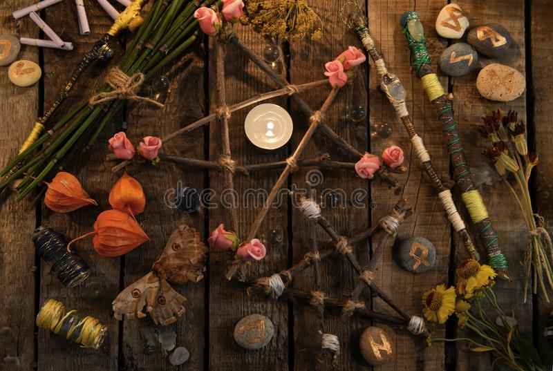 Pentagrammi con le bacchette, il lepidottero, le rune ed i fiori magici sulla tavola della strega, vista superiore fotografia stock libera da diritti