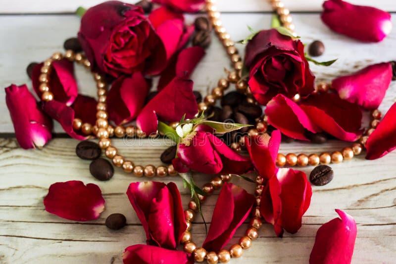 Pentals delle rose rosse e di una collana fotografia stock libera da diritti