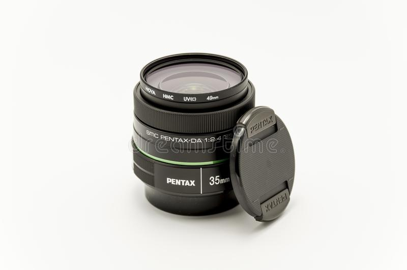 Pentax 35 mm lens f2.4 brand new. A Pentax 35 mm lens - f2.4 brand new, out of the box with a UV filter attached on a white background stock images