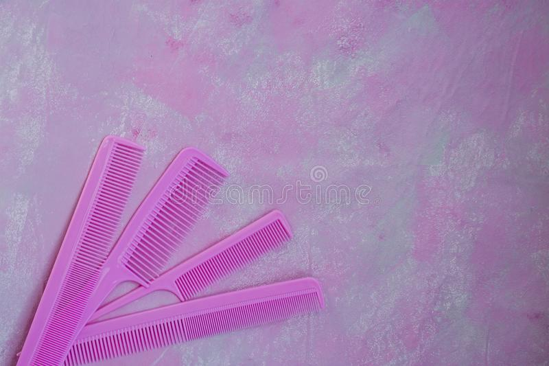 Pente brilhante cor-de-rosa para cabeleireiro Bar da beleza Ferramentas para os penteados Fundo cor-de-rosa barbershop Grupo de e fotografia de stock