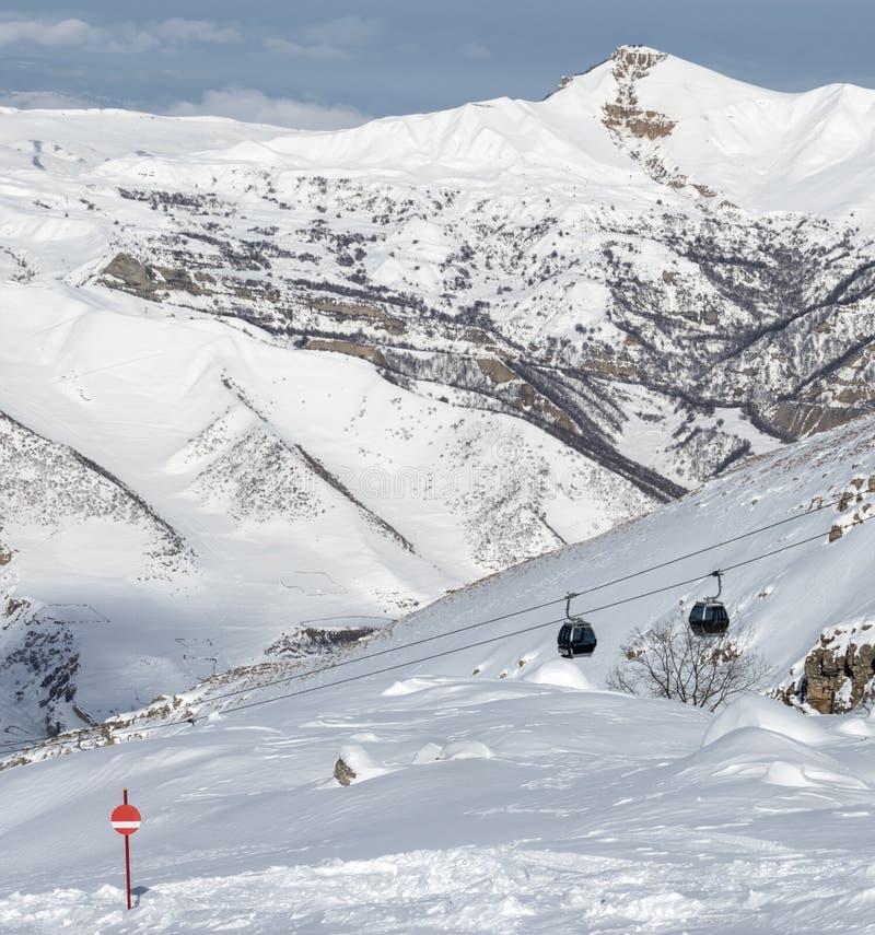 pente couverte de neige de ski dans les montagnes et l'ascenseur neigeux de gondole photographie stock