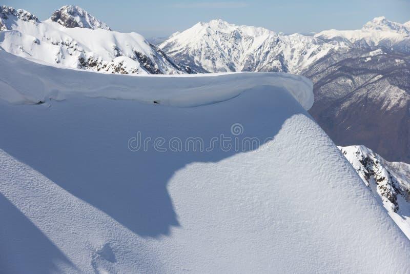 Pente de montagne et corniche de neige photo stock