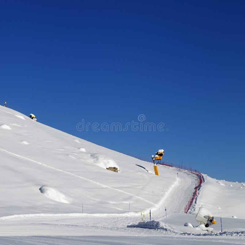 Pente de ski avec snowmaking au jour du soleil photographie stock libre de droits