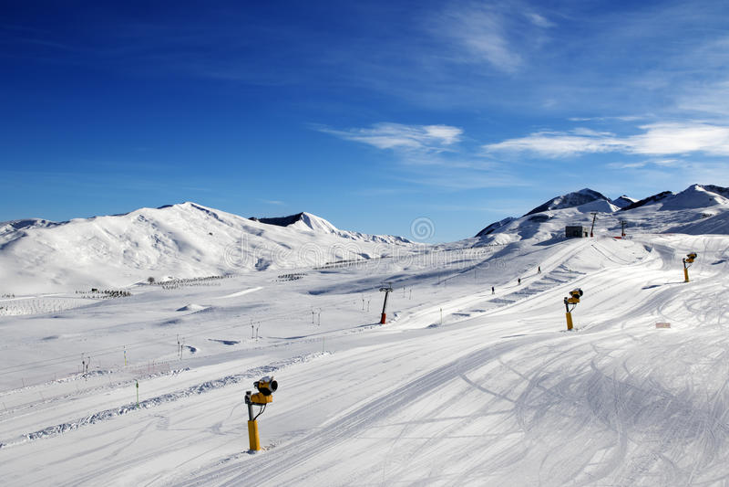 Pente de ski avec snowmaking au jour du soleil image stock