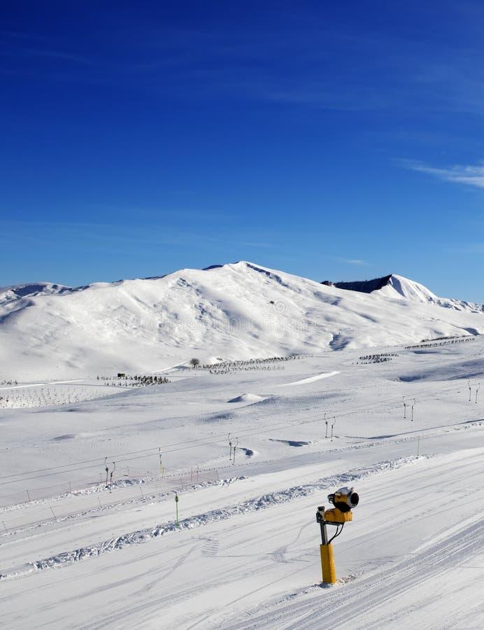 Pente de ski avec snowmaking au jour du soleil images libres de droits