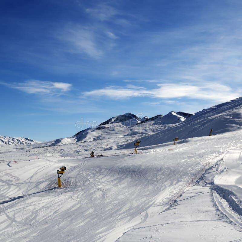 Pente de ski avec snowmaking au matin du soleil photographie stock