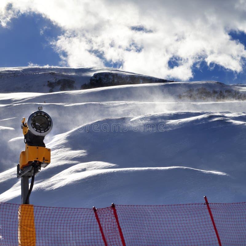Pente hors-piste pendant le ciel bleu de tempête de neige et de lumière du soleil avec le nuage photographie stock