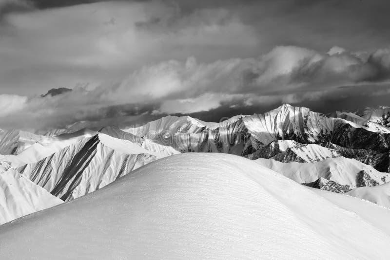 Pente neigeuse hors-piste noire et blanche et montagnes nuageuses images stock