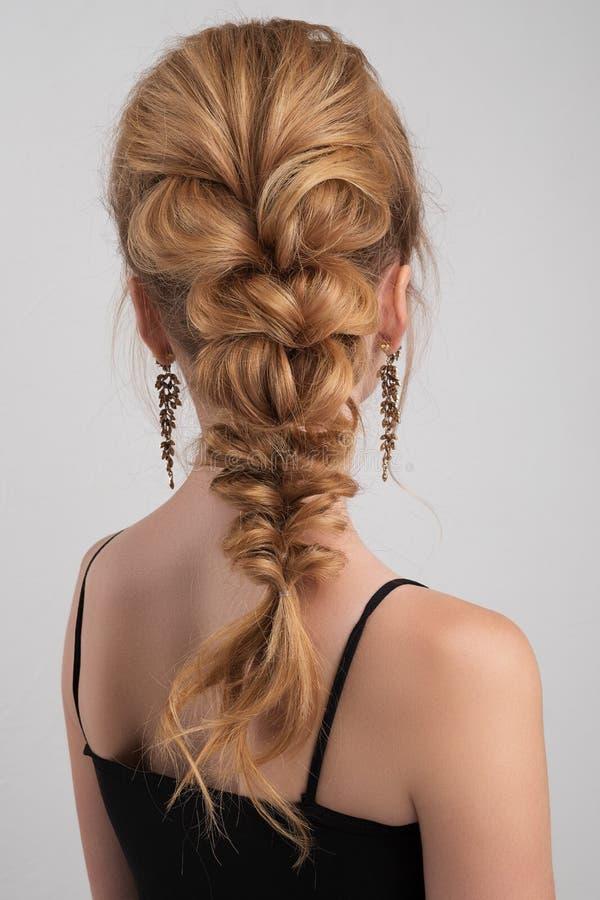 Penteado da noite cabelo altamente recolhido em uma trança na menina loura foto de stock