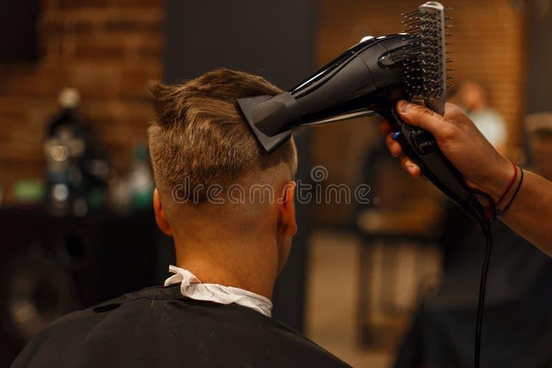 Penteado do ` s dos homens Cabelo que denomina com um secador de cabelo barbershop fotos de stock