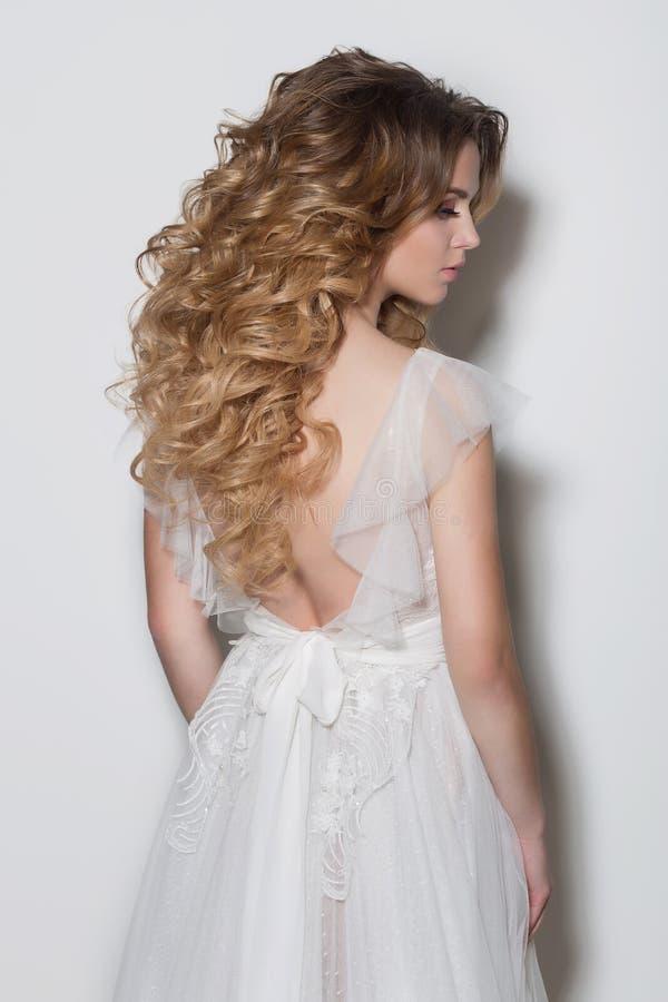 Penteados elegantes bonitos para a noiva delicada bonita das moças em um vestido de casamento bonito em um fundo branco no th fotografia de stock royalty free