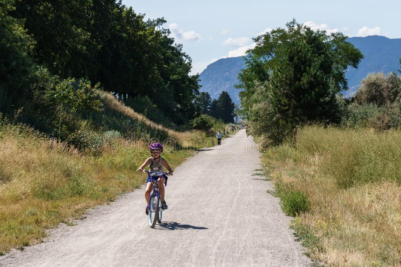 Penticton, Canada - August 04, 2018 : Girl on a bike on Kettle Valley Railway biking trail. Summer day near Penticton British Columbia Canada stock images