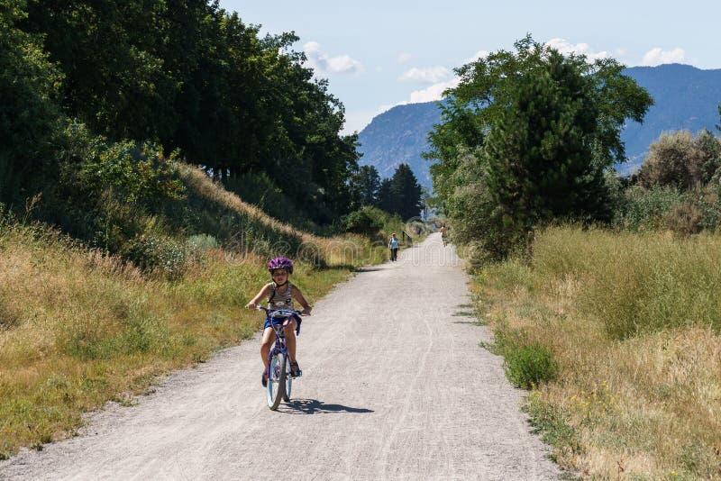 Penticton Kanada - Augusti 04, 2018: Flicka på en cykel på järnväg cykla slinga för kokkärldal arkivbilder