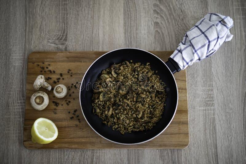 Pentola con il risotto dei funghi su un tagliere di legno decorato con aglio, pepe, il limone ed i funghi immagine stock libera da diritti