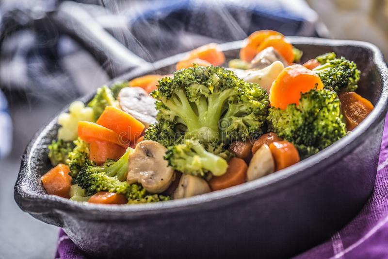 Pentola del vegano Alimento vegetariano - i funghi della carota dei broccoli salano il pepe su burro immagini stock
