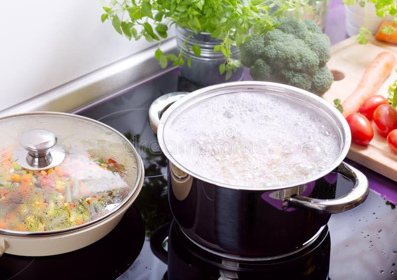 Pentola di acqua bollente con gli spaghetti sul fornello fotografie stock