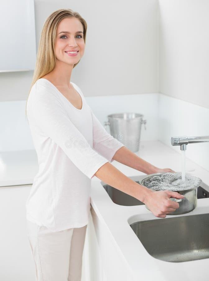Pentola di riempimento della donna splendida allegra con acqua fotografia stock libera da diritti